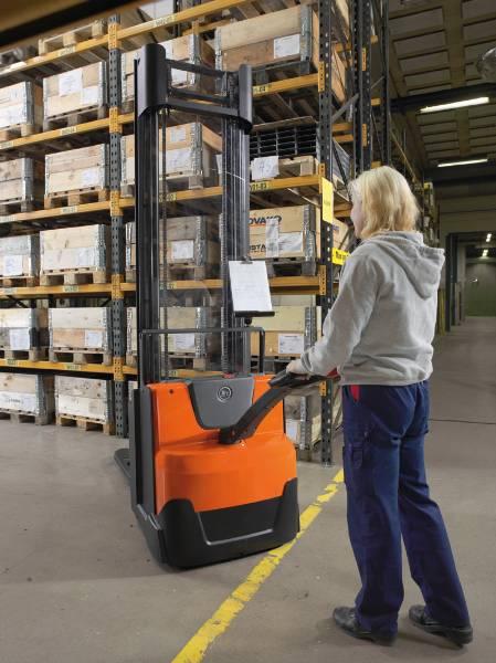Woman using a walkie stacker in narrow warehouse aisles