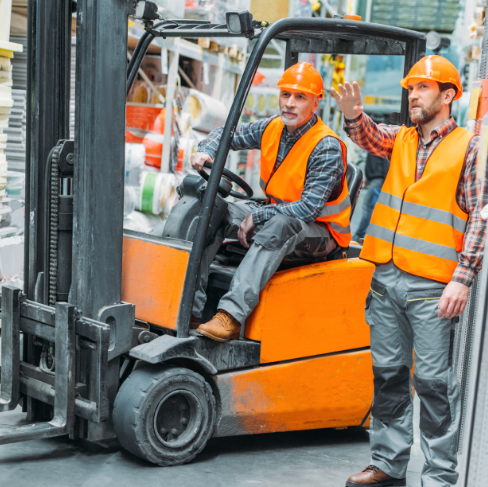 Male workers in a lift truck discussing OSHA forklift regulations