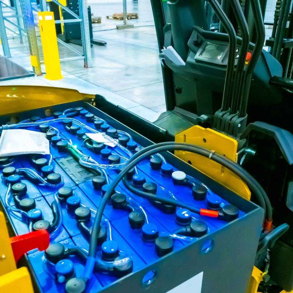 Electric forklift undergoing forklift battery maintenance in a warehouse