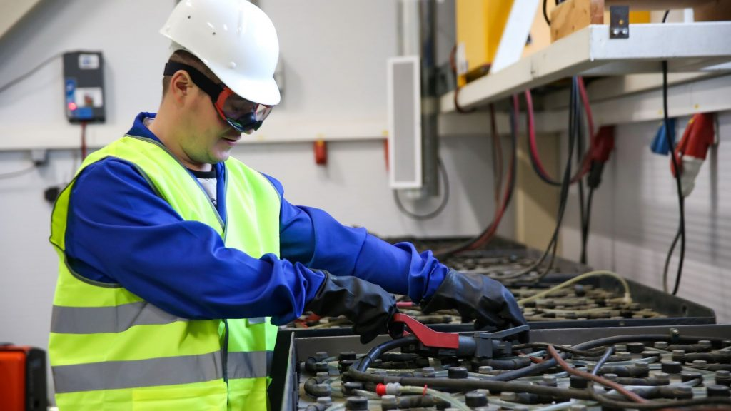 Electrical technician performing forklift battery watering and charging
