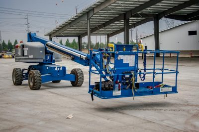 Green and white boom lift being used outdoors