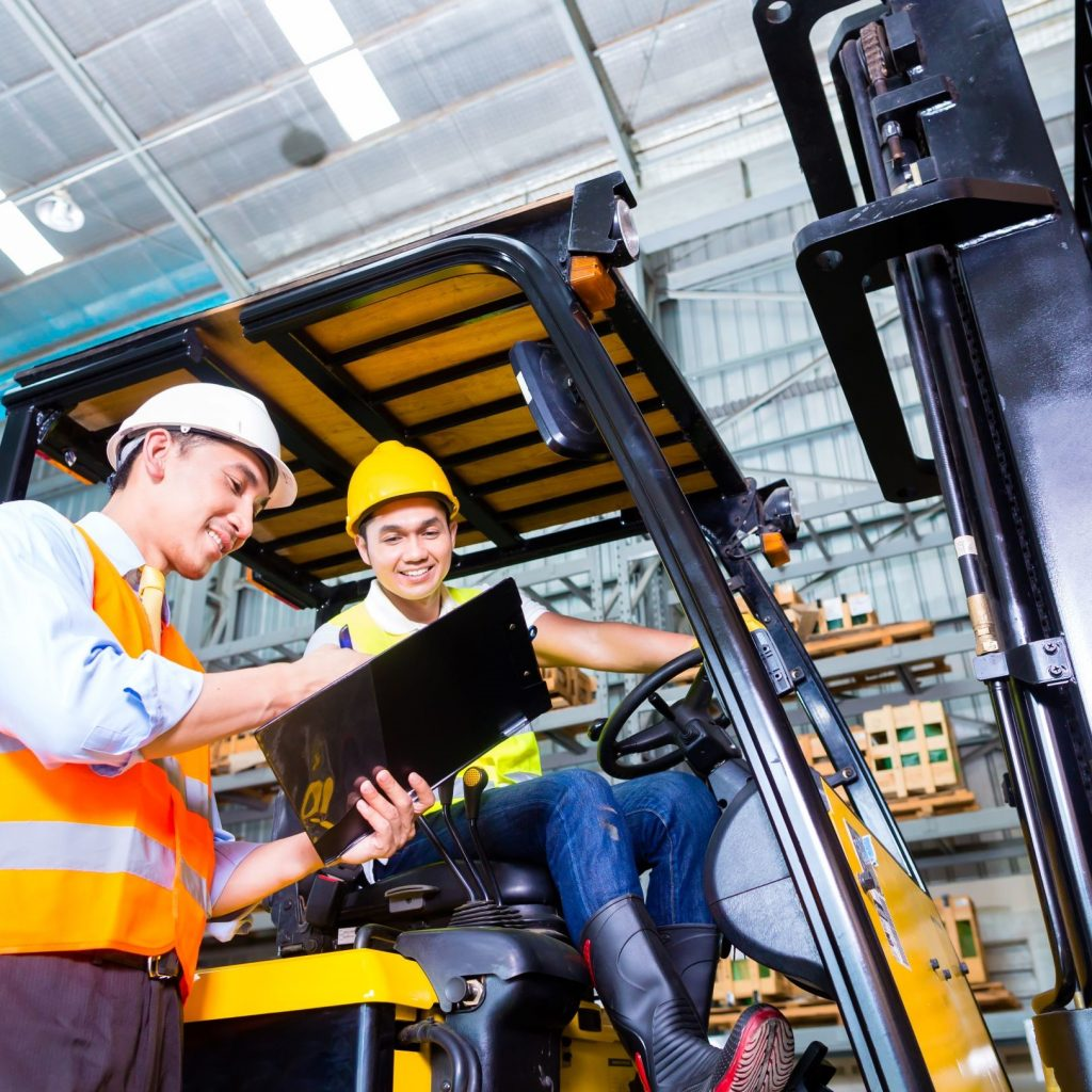 Two male workers following forklift safety tips in a warehouse