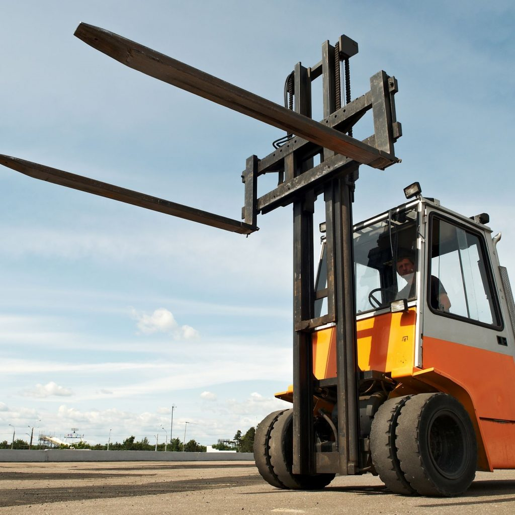 Small forklift with raised forklift tines outside on the pavement