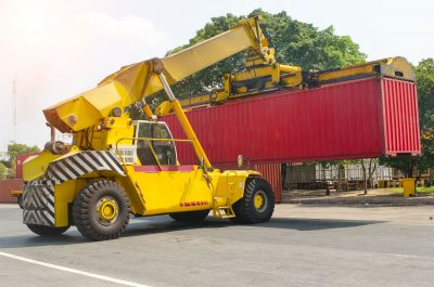 Large yellow reach stacker carrying a shipping container