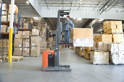 Small order picker lift used by an operator in a crowded warehouse