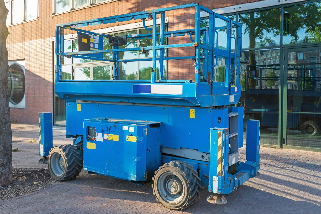 Compact all-terrain scissor lift sitting outside on the pavement