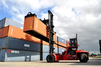 Top pick container handler transporting a loaded container