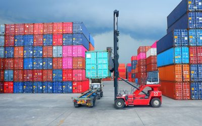 Red container handler for sale loading a shipping container onto a truck