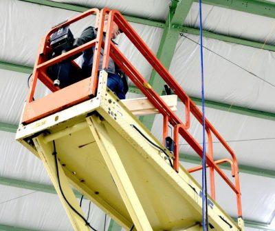 Narrow scissor lift being used indoors