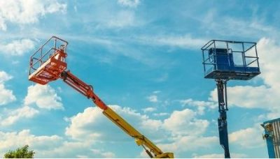 Two straight mast boom lifts extended outside