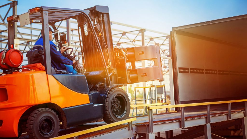 Counterbalance forklift with a forklift clamp unloading a semi-truck
