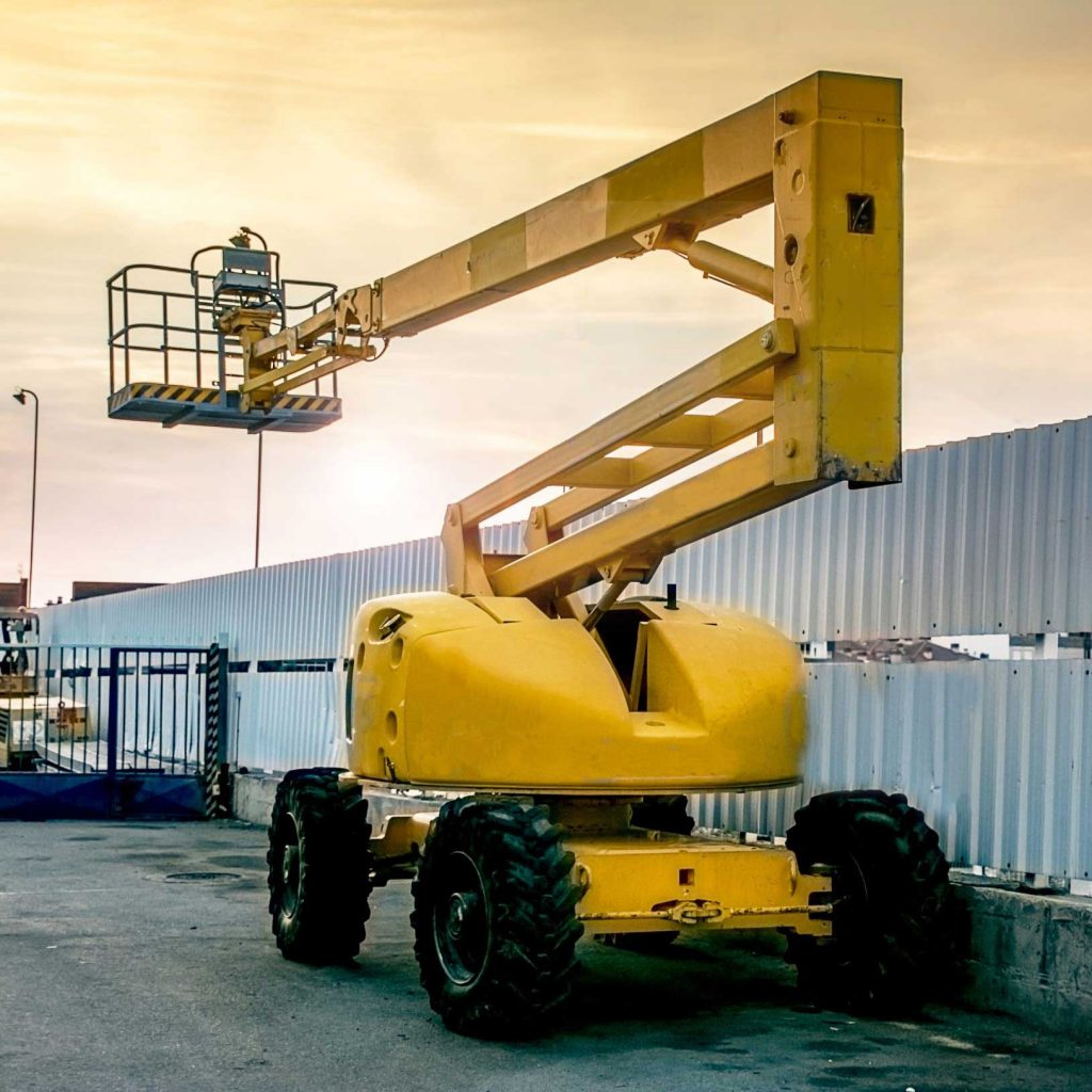 Yellow aerial boom lift parked at an industrial site