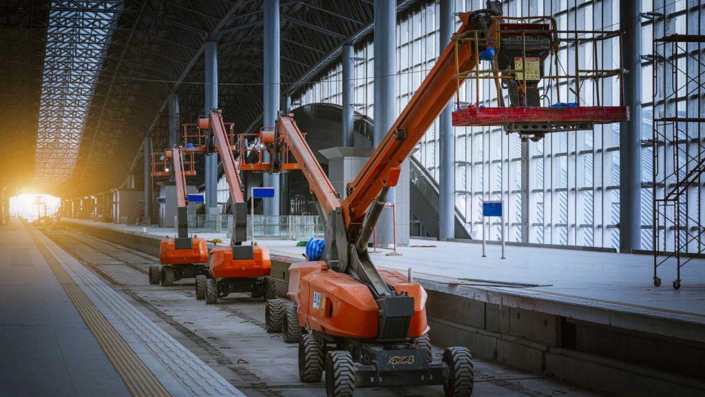 Four boom lifts working on public transportation tracks