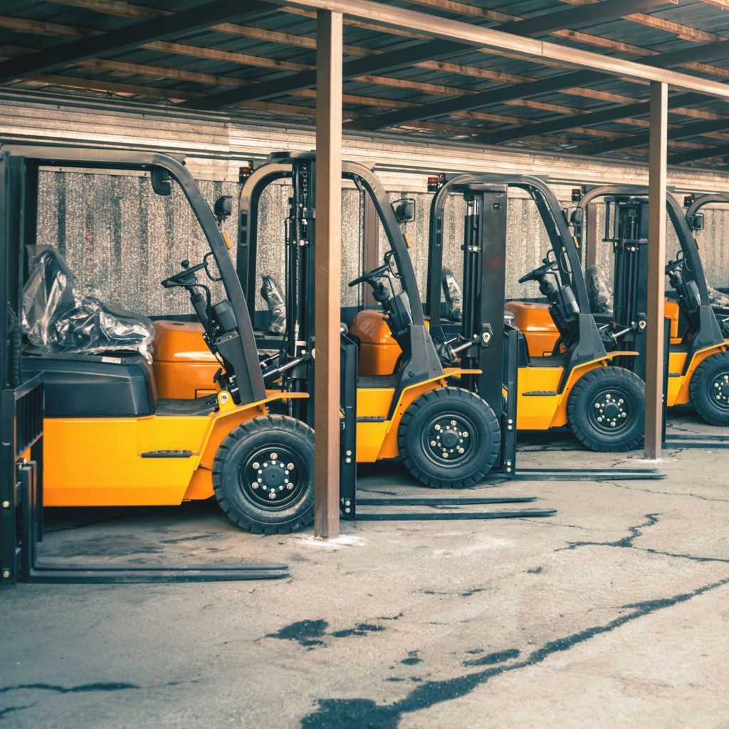 Four yellow forklifts under an awning
