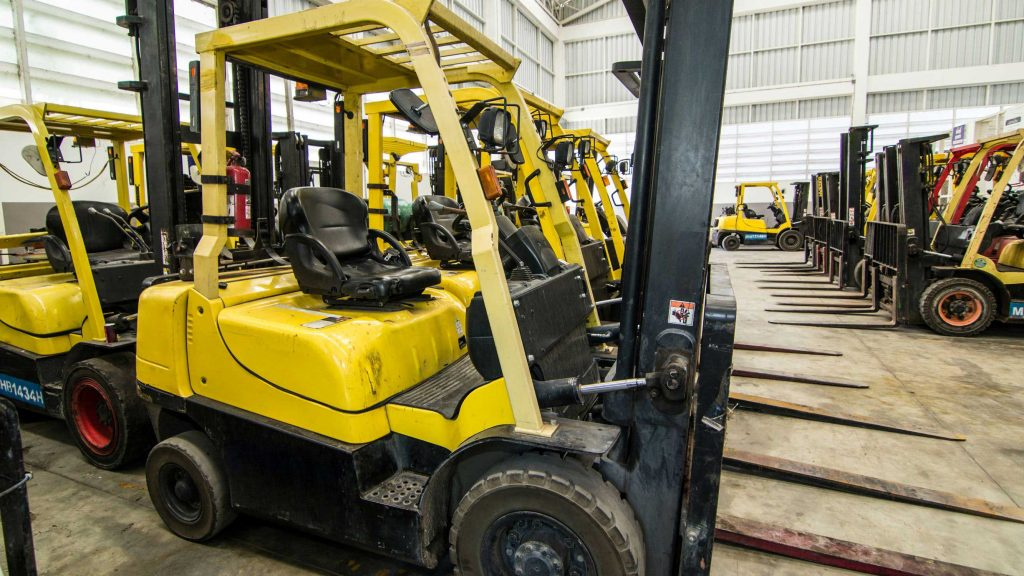 Rows of used forklifts inside a large warehouse