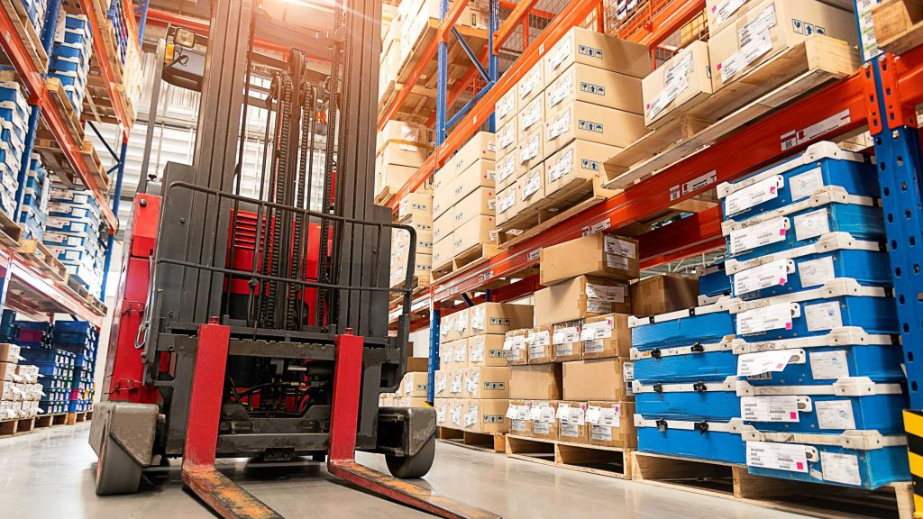 Counterbalance forklift parked among warehouse aisles