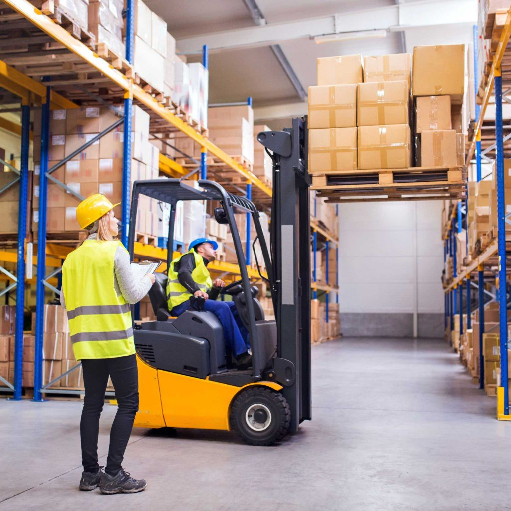 Two male forklift operators checking functionality of forklift safety features