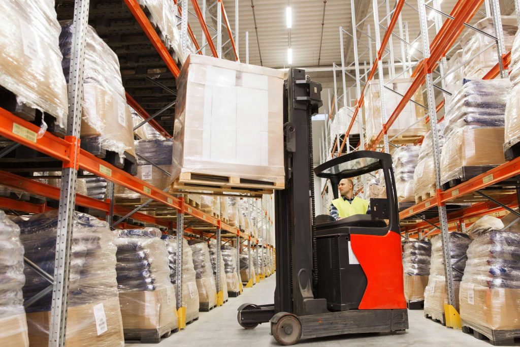Small red warehouse forklift used by a standing operator