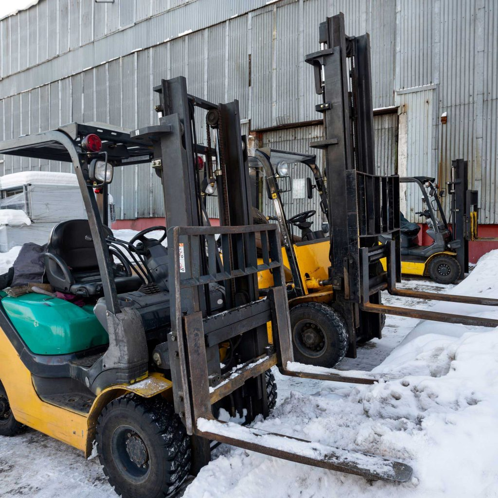 Three yellow forklifts parked in the snow