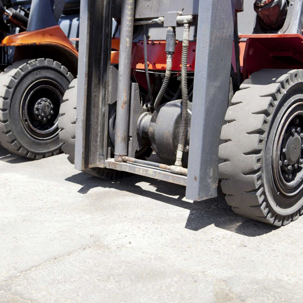 Closeup of the tires on two orange counterbalance forklifts