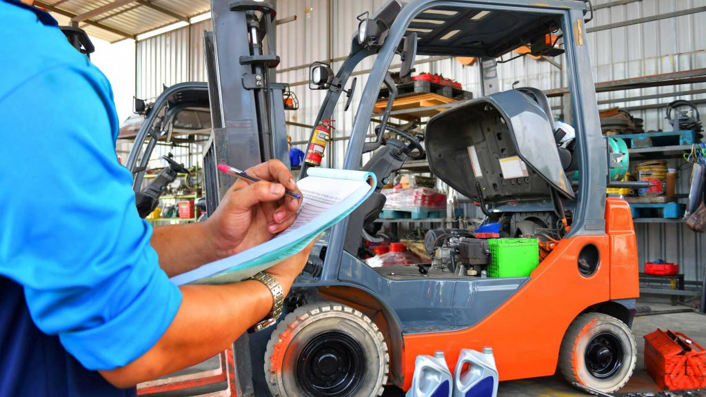 Operator documenting maintenance issues on a forklift daily checklist
