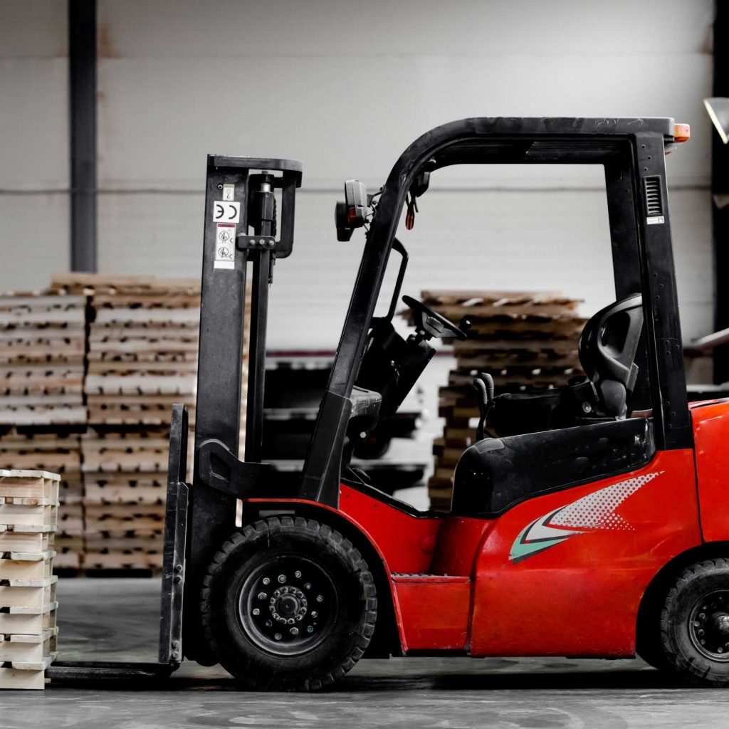 Red counterbalance forklift in a warehouse surrounded by pallets
