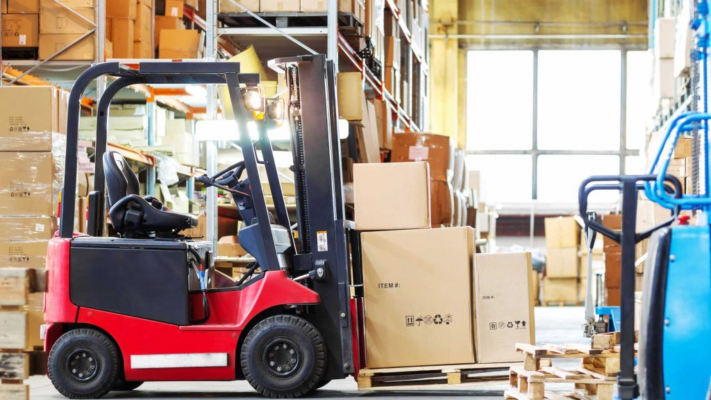 Red electric forklift loaded with boxes on a pallet