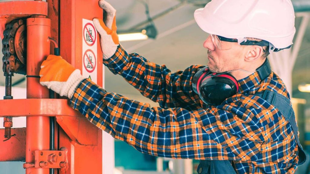 A warehouse operator conducting forklift maintenance on an orange vehicle.