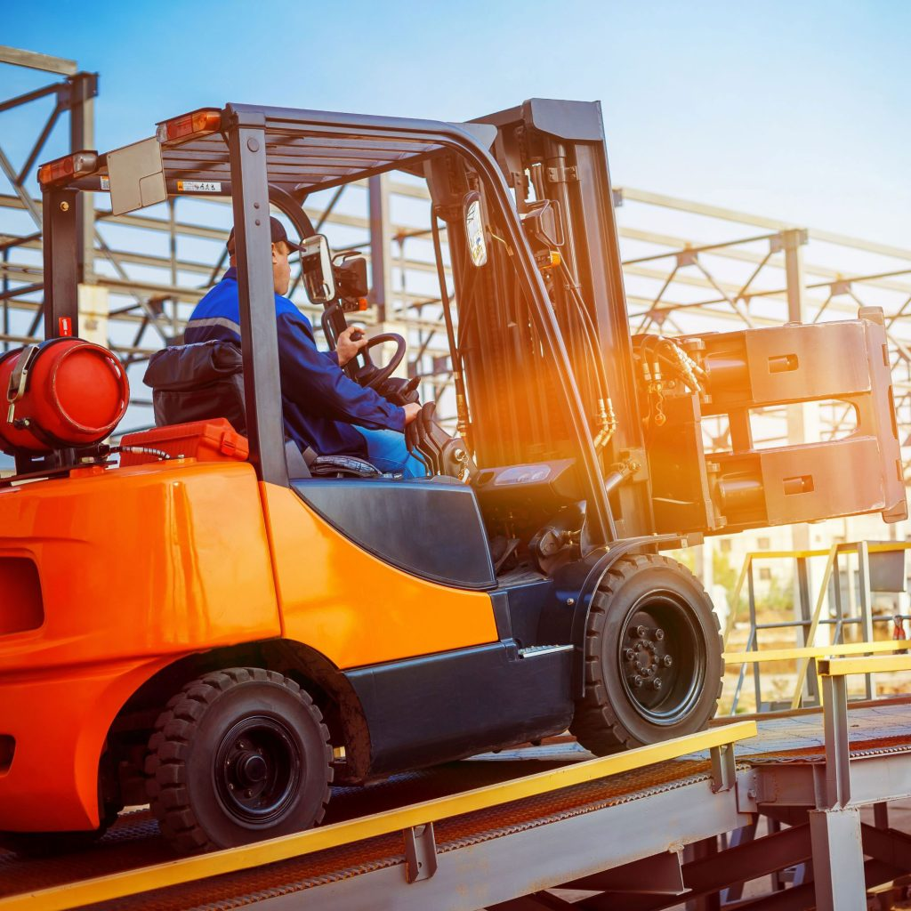 An operator showing how to operate an orange sit-down forklift safely.