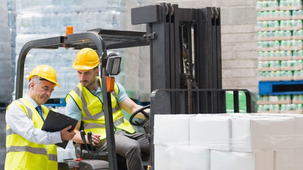 Two warehouse workers reading a guide on how to drive a forklift.