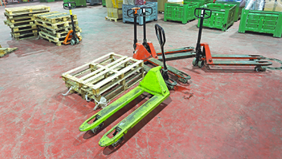Manual pallet jacks for sale in a warehouse.