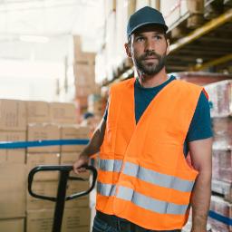 A warehouse worker pulling manual pallet jacks behind him.