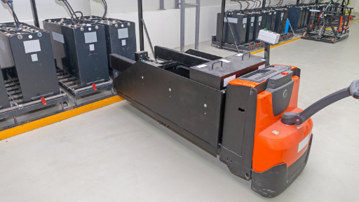 Orange and grey electric pallet jacks in a warehouse.
