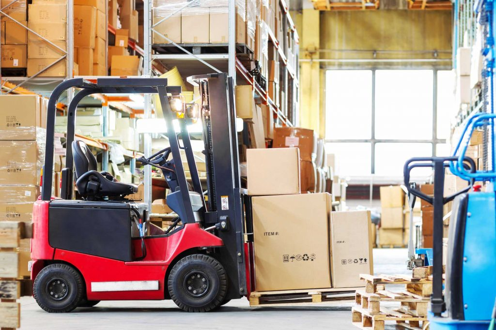 Red counterbalance forklift carrying a pallet with boxes on it
