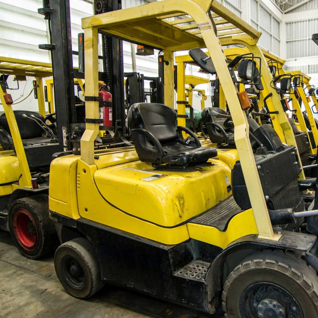 Forklift safety procedures being demonstrated on a lot of yellow trucks in a warehouse.