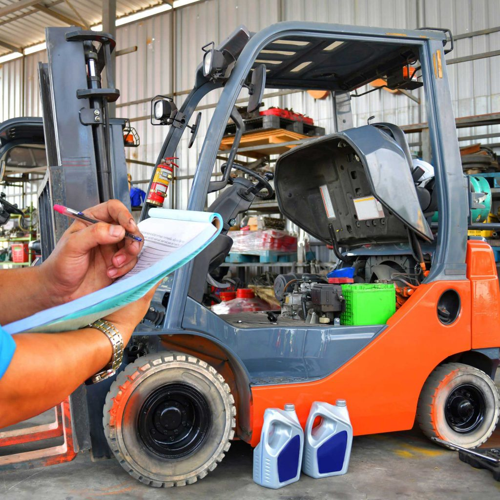 Warehouse forklift in a repair shop getting a hydraulic fluid change