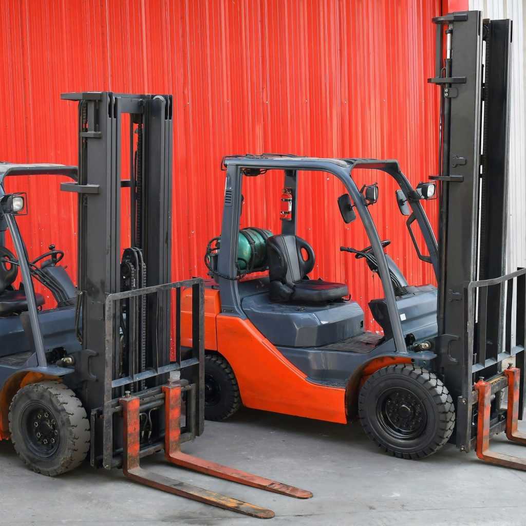 Different types of forklifts in an outdoor garage.