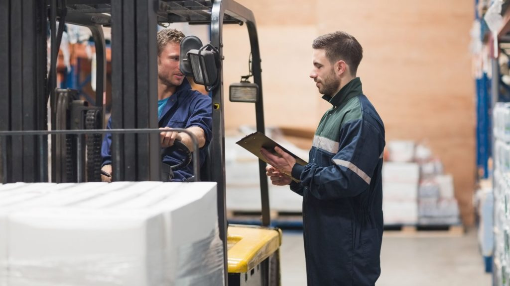 Two operators in forklift training, learning how to drive a forklift with its forklift controls.
