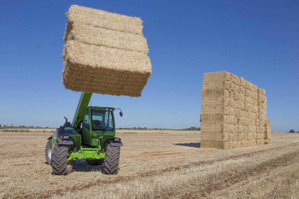Telehandler lift transporting bales of hay on a farm