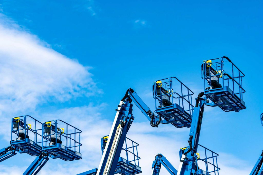 Multiple used boom lifts for sale extended towards the sky outside