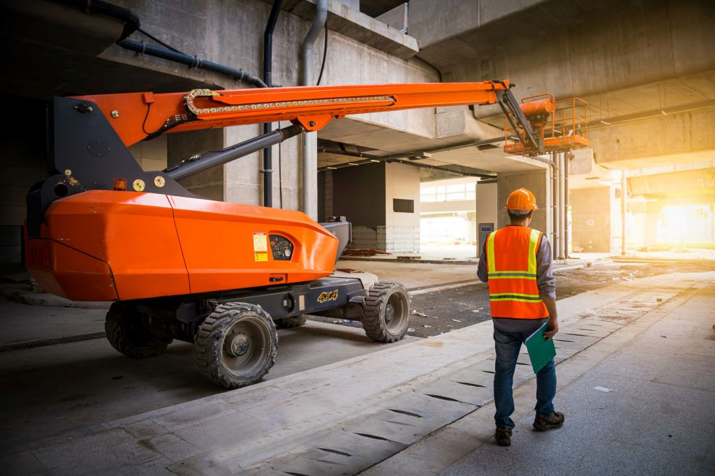 Worker standing next to a large orange boom lift