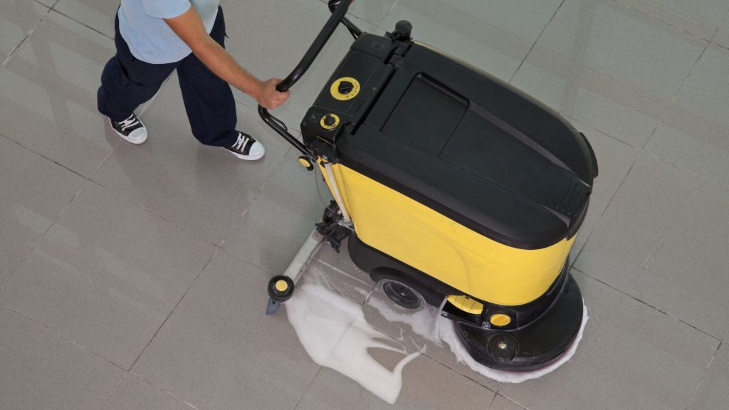 Maintenance worker using a scrubber for commercial floor cleaning