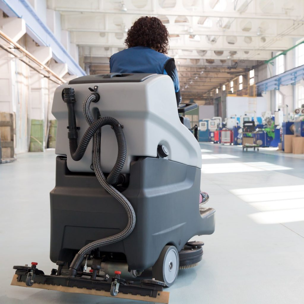 Industrial cleaning with a ride-on scrubber indoors