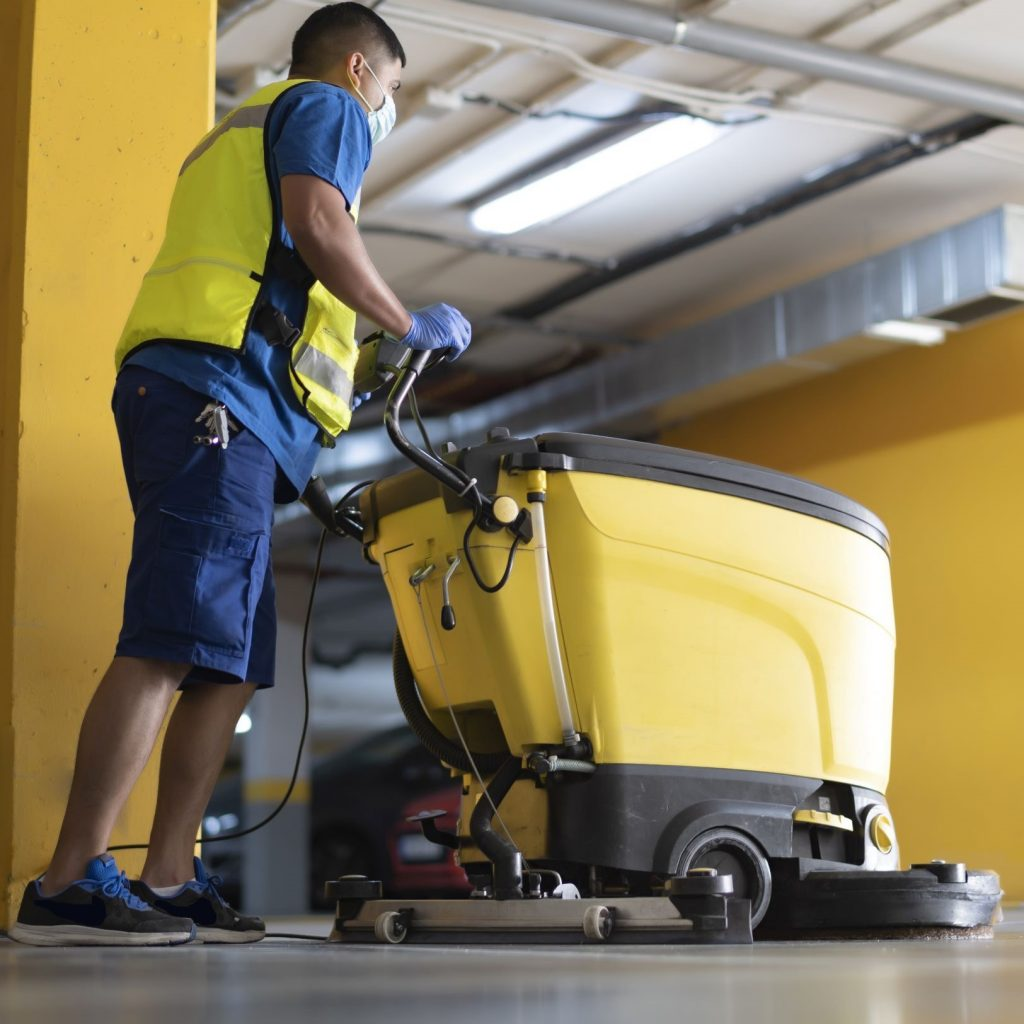 Industrial floor cleaning machines being used in an indoor facility