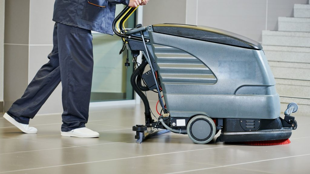 Worker using janitorial floor cleaning equipment at an indoor facility