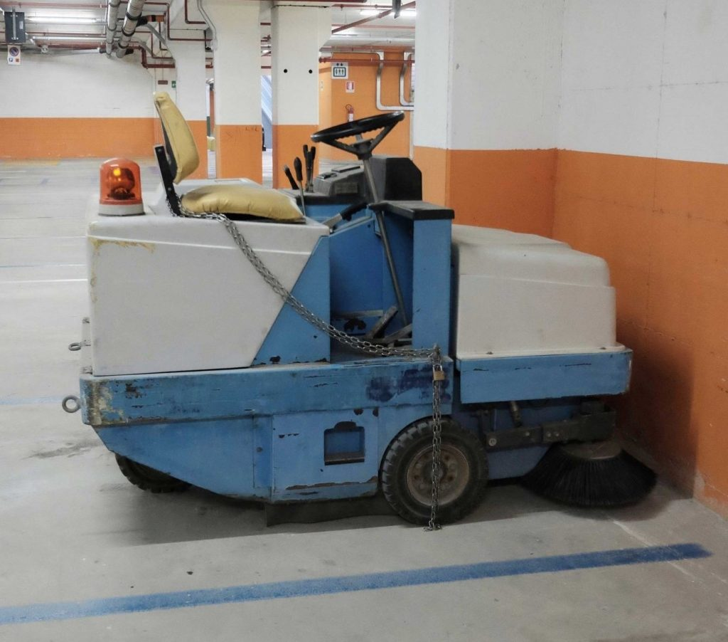 Combination sweeper-scrubber parked in a covered parking garage
