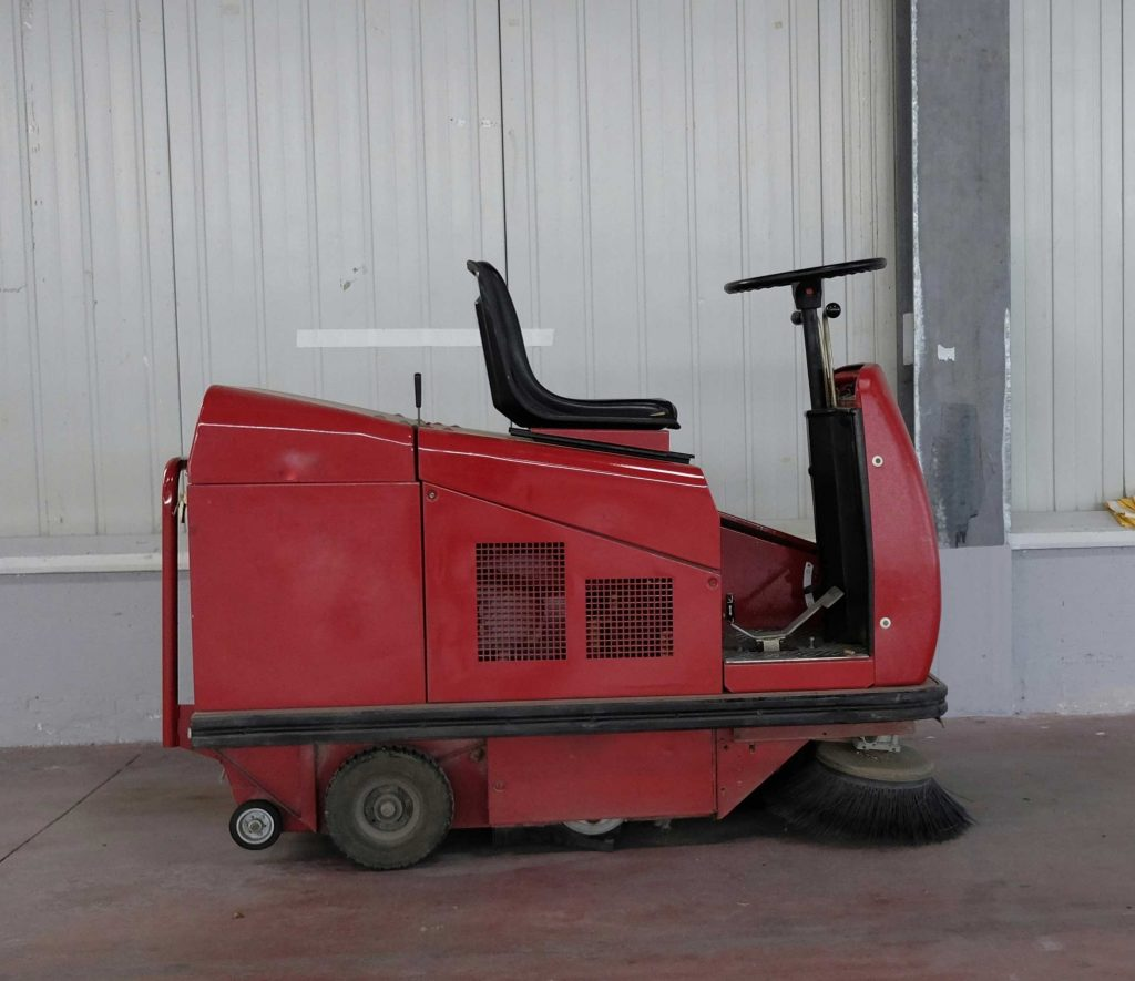 Sweeper-scrubber indoors on a dirty floor