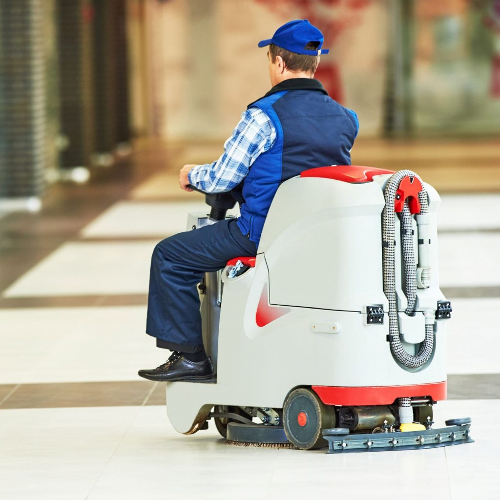 Male worker riding a floor scrubber machine through school hallways