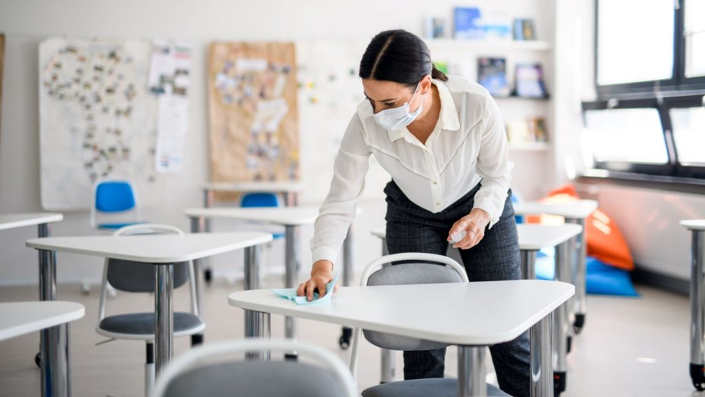Female teacher classroom cleaning before students arrive