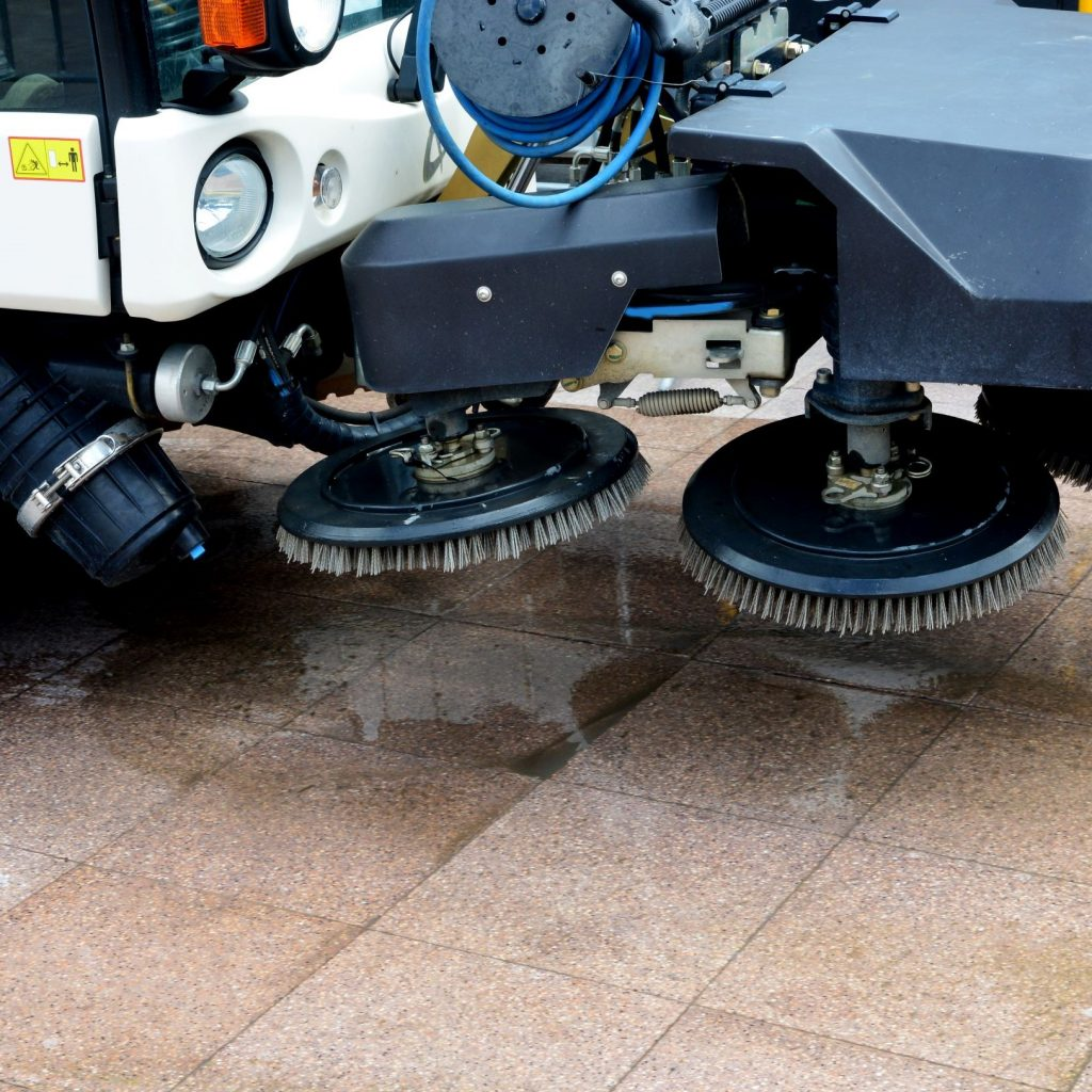 Wet floor machine brushes attached to the front of an industrial scrubber